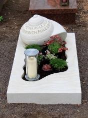 Urnengrab mit wellenförmiger Einfassung und Schnecke als Grabmal
